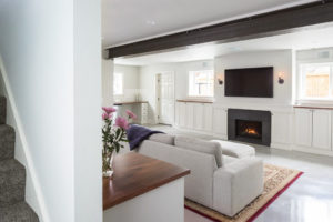 Remodeled basement facing the fireplace with tv mounted above