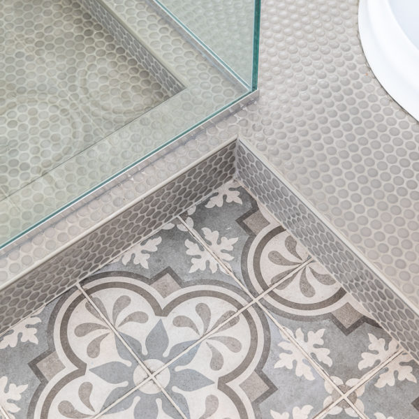 Grey mosaic floor tile closeup and penny rounds in bathroom